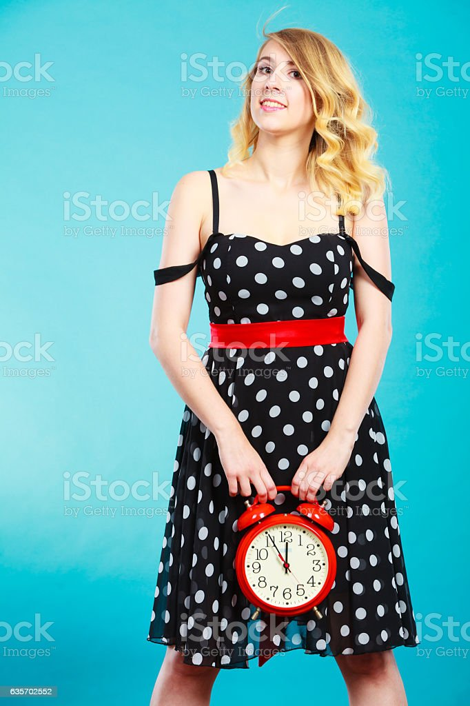 Smiling girl with alarm clock on blue. royalty-free stock photo