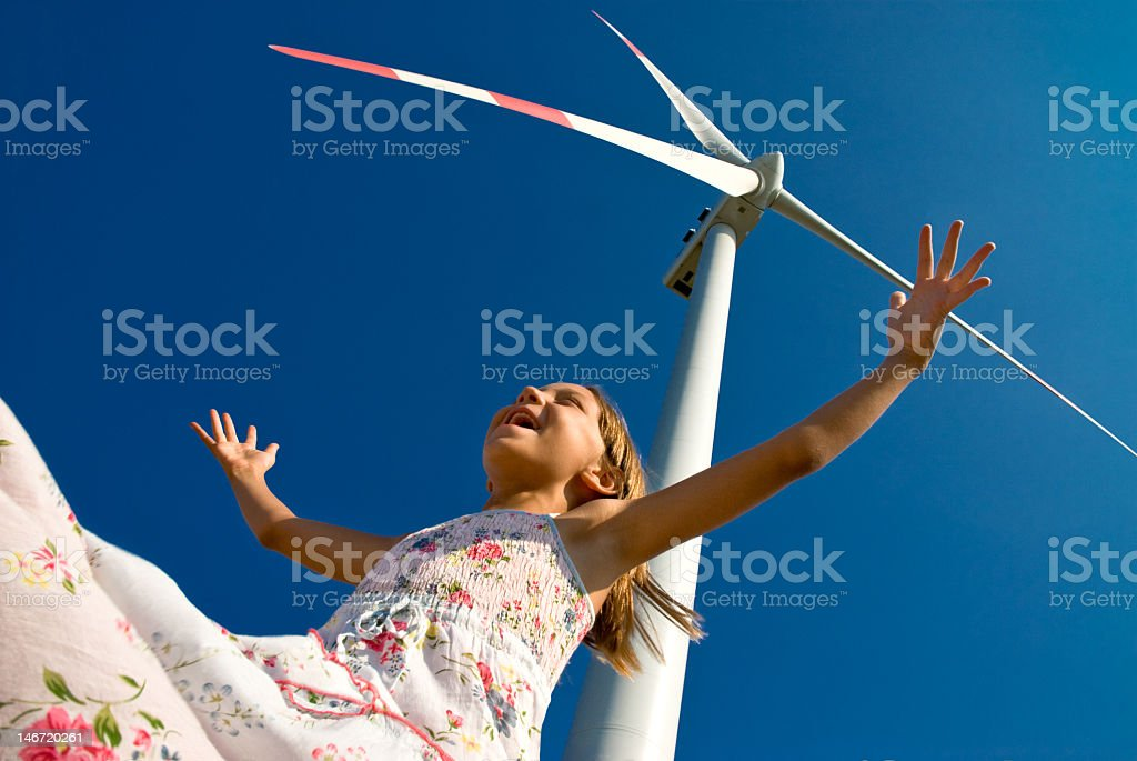 Smiling girl with arms outstretched below a windmill stock photo