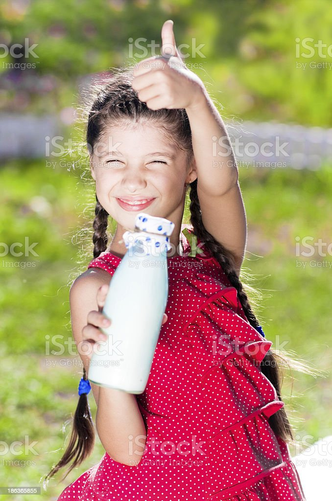 Smiling girl with bottle of milk shows thumb up royalty-free stock photo