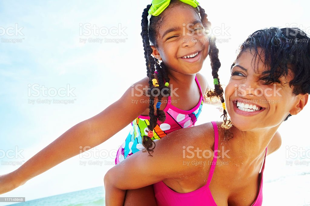 Smiling girl with braids carried piggyback style by woman stock photo