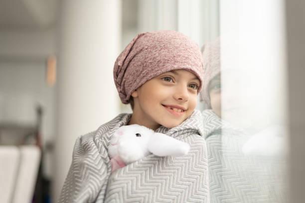 lächelndes mädchen mit krebs schaut aus dem fenster - krebs tumor stock-fotos und bilder