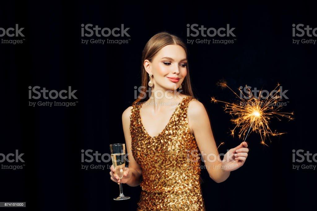 Smiling girl with Christmas sparkler – zdjęcie