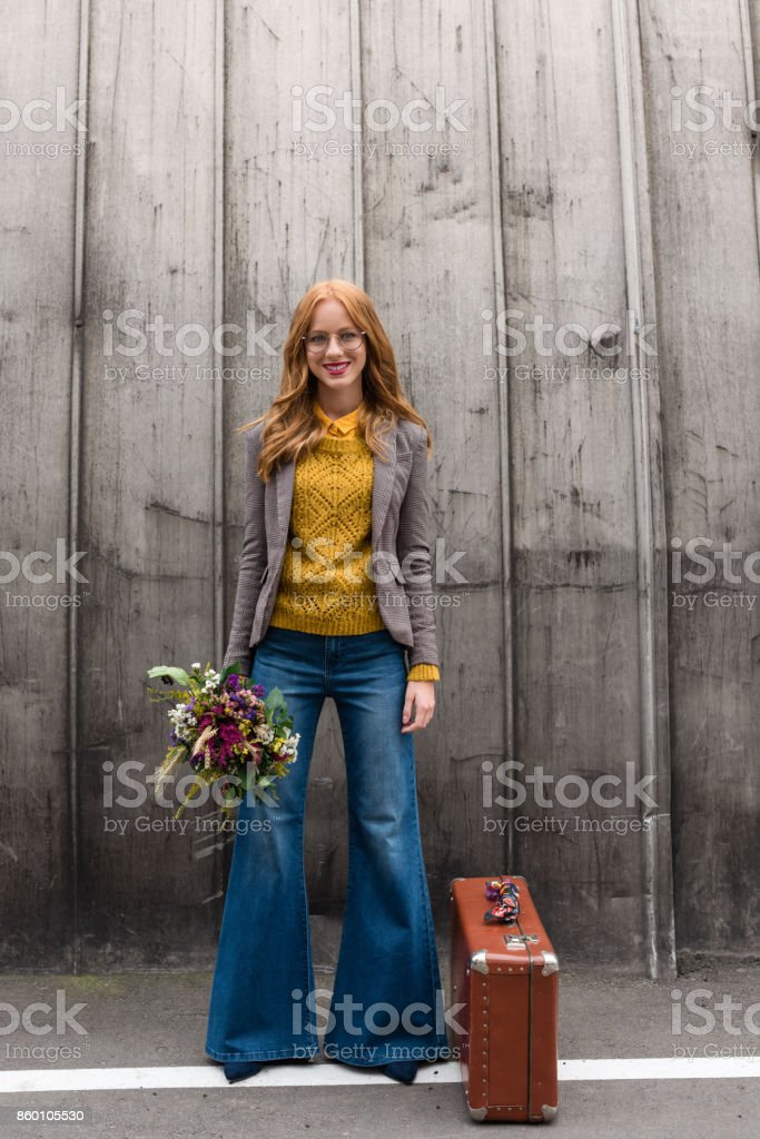 smiling girl with flowers and suitcase stock photo