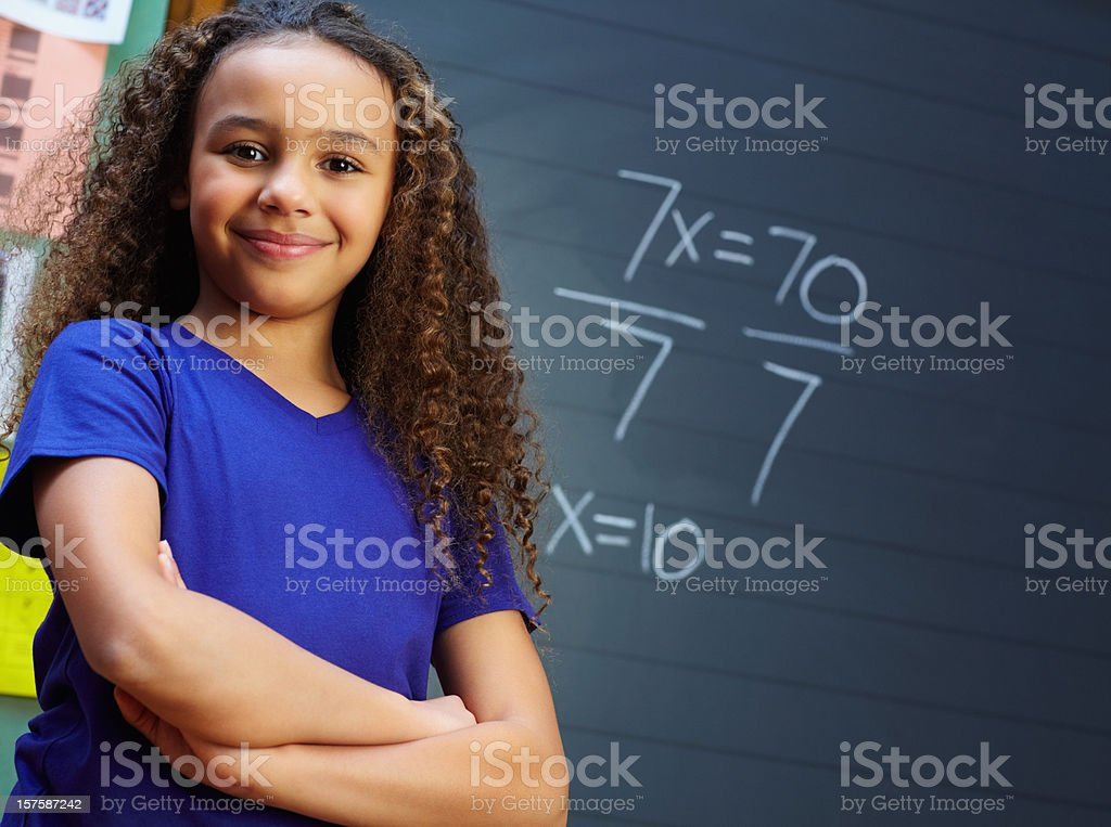 Smiling girl with hands folded against the blackboard royalty-free stock photo