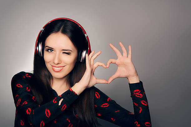 Smiling Girl with Headphones Making Heart Sign stock photo