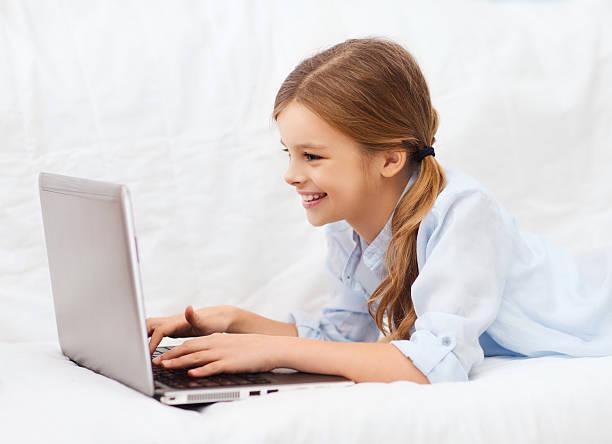 lächelnd mädchen mit laptop-computer zu hause - kostenlose onlinespiele stock-fotos und bilder