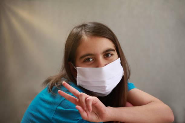 Lächelndes Mädchen mit Maske und Siegeszeichen – Foto