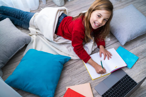 Smiling girl with notebook and laptop stock photo