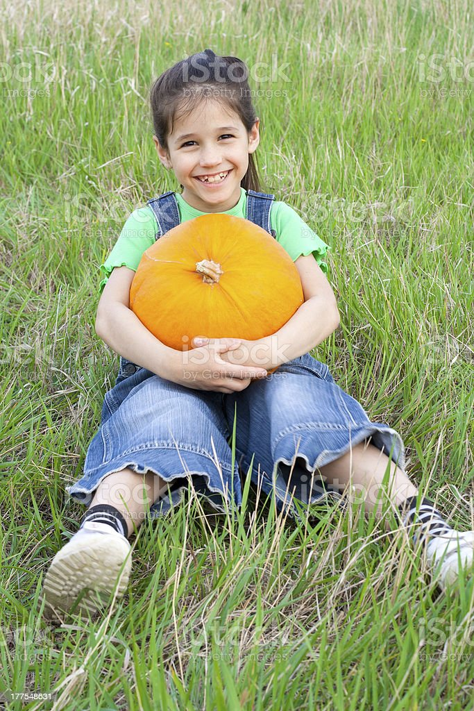 Smiling girl with pumpkin royalty-free stock photo
