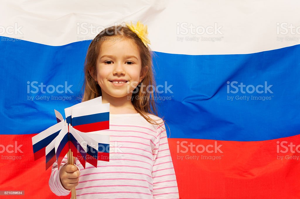 Smiling girl with set of flags in her arms stock photo