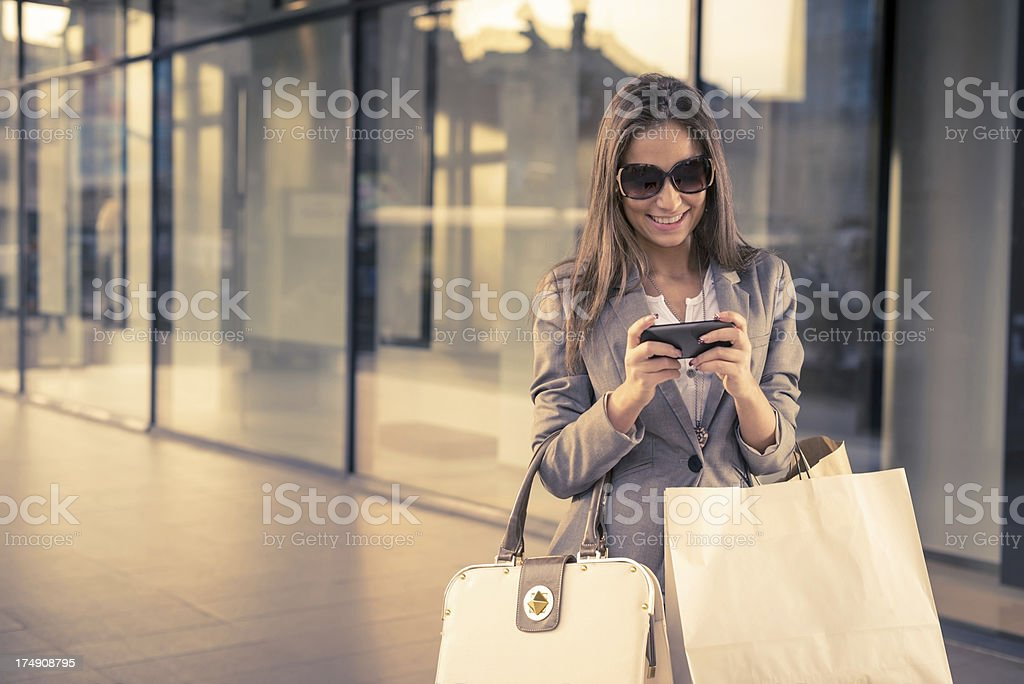 Smiling girl with shopping bags, texting stock photo