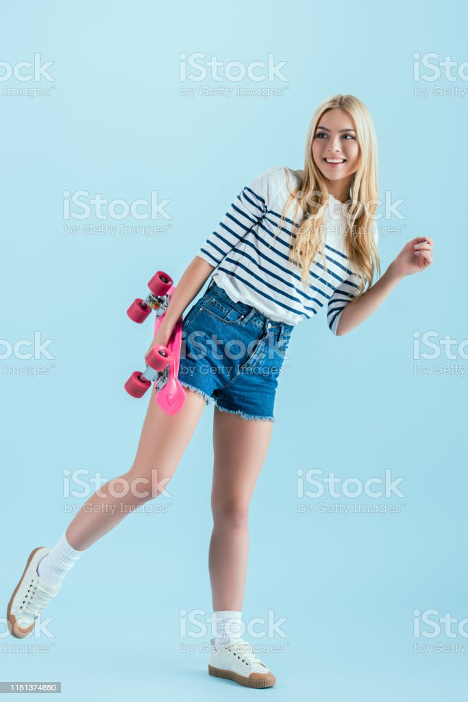 Smiling girl with skateboard standing on one leg isolated on blue