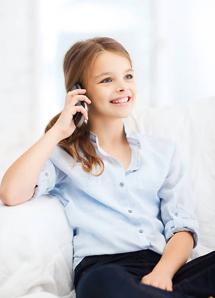 lächelnd mädchen mit smartphone zu hause - iphone gratis stock-fotos und bilder