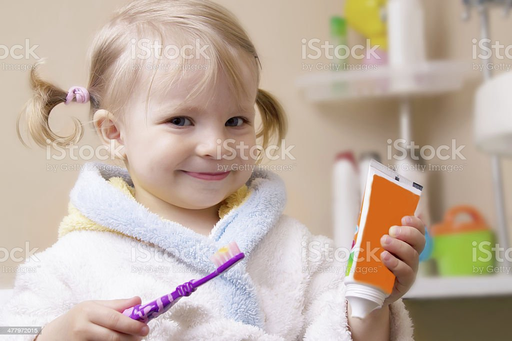 Smiling girl with toothbrush and tube stock photo