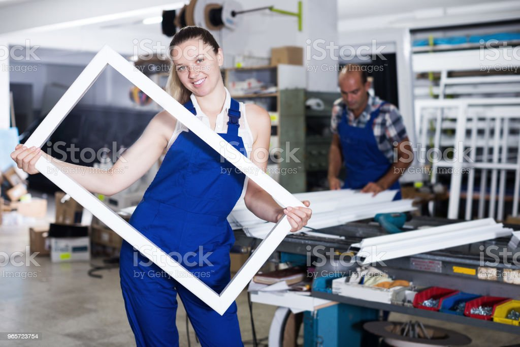 Smiling girl worker with plastic window frame - Royalty-free 20-29 Years Stock Photo