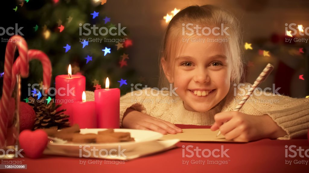Smiling girl writing list of presents for family before holidays,...