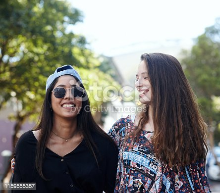 Two smiling girlfriends stand together in a leafy park, smiling and relaxed.