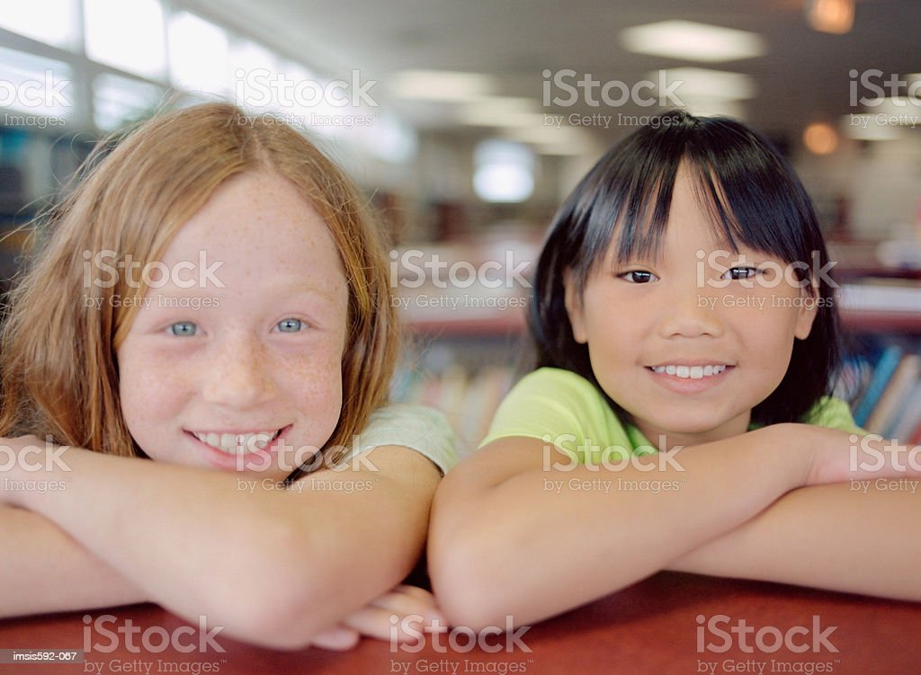 Smiling girls in library royalty-free stock photo