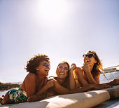 Multiracial group of girls relaxing and laughing on a private yacht deck. Female friends sunbathing on the bow of a boat.