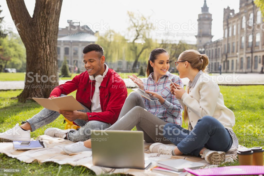 Smiling girls sitting near busy fellow student royalty-free stock photo