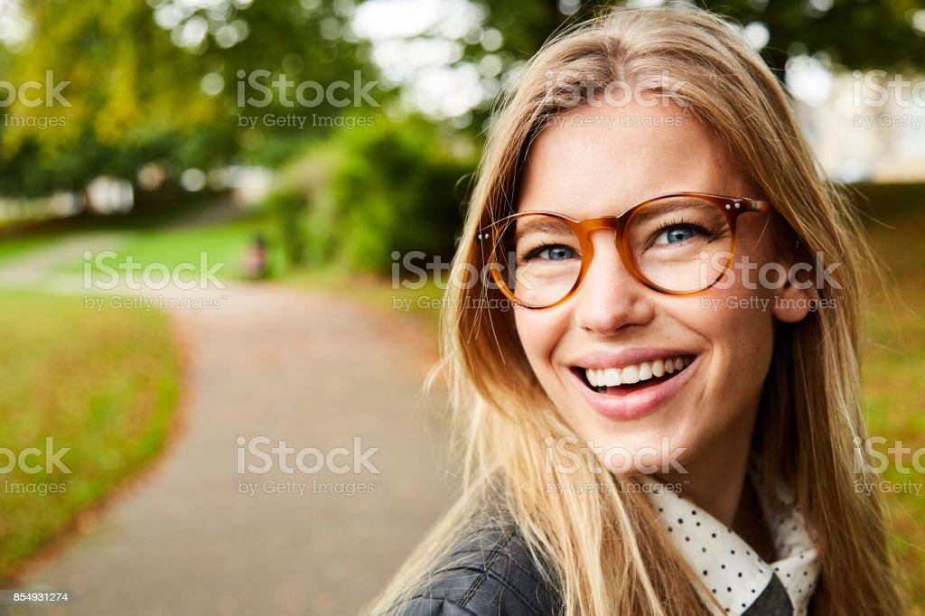 Smiling glasses girl in park stock photo