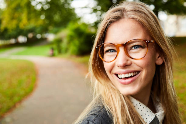 Smiling glasses girl in park stock photo