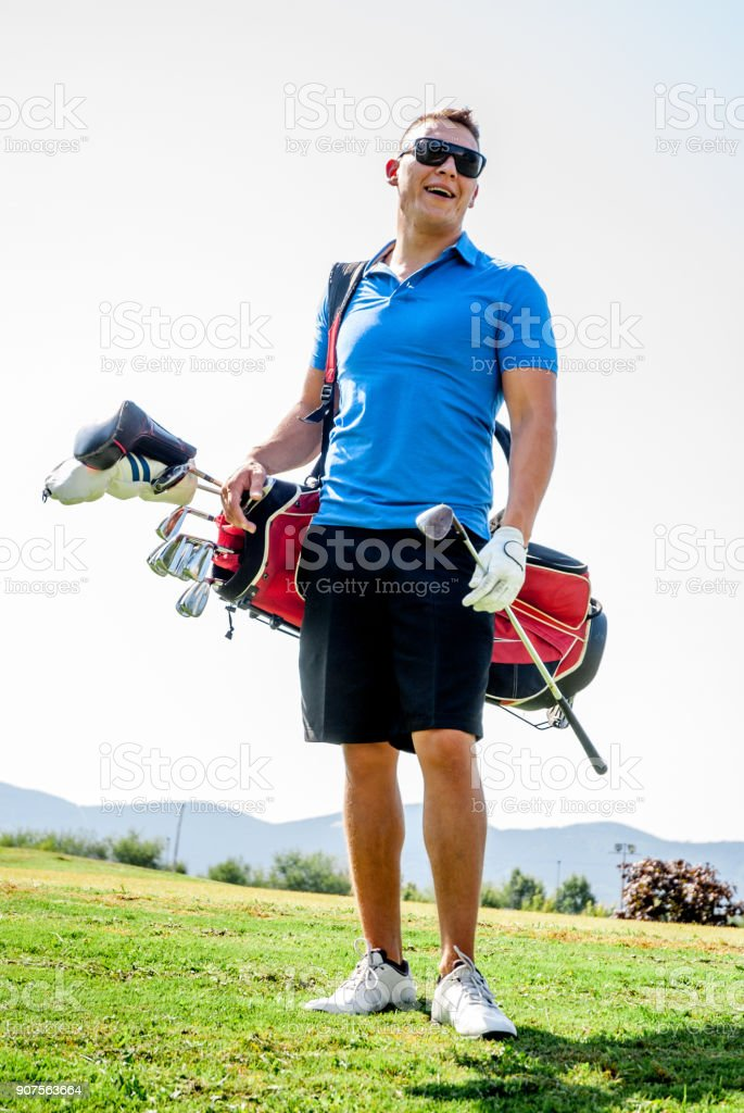 Smiling Golf Player with Sunglasses Carrying Golf Bag and Holding...