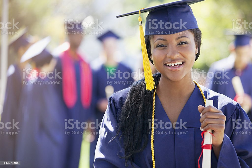 Smiling graduate holding diploma stock photo