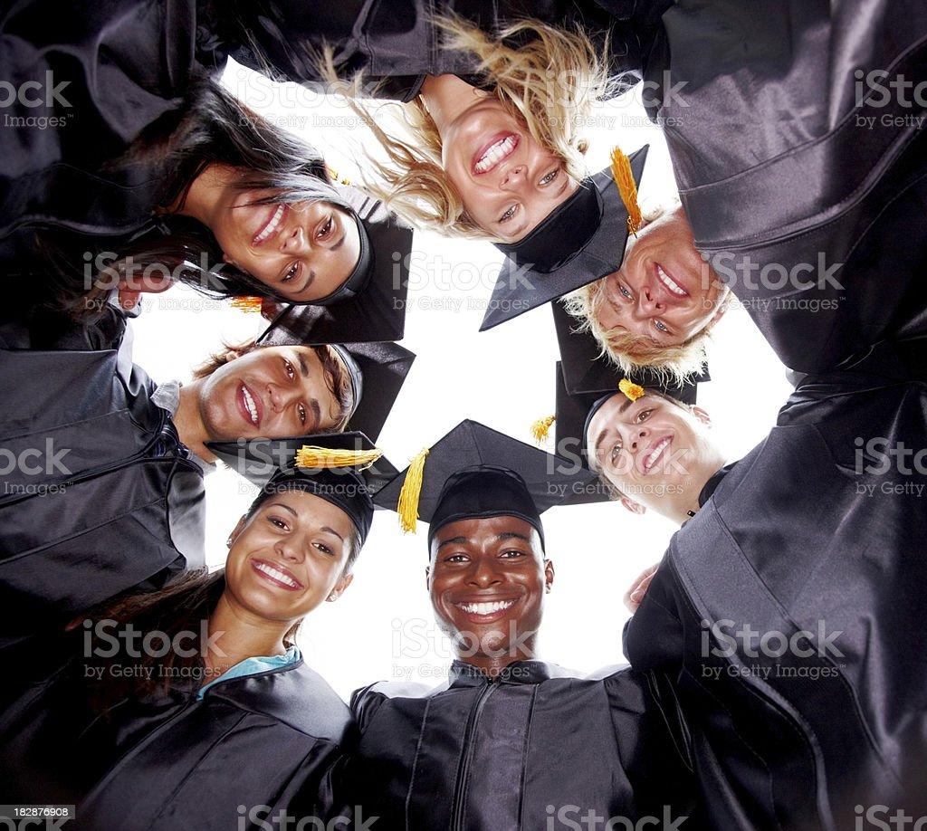 Smiling graduate students making a huddle stock photo