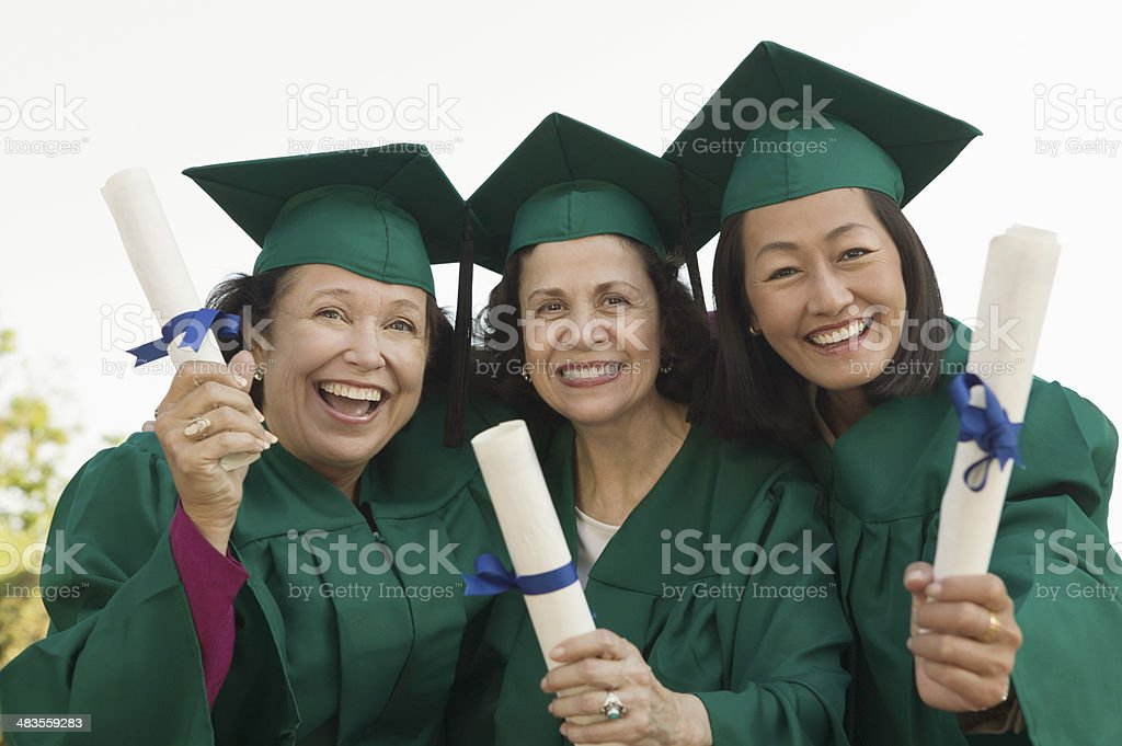Smiling Graduates Holding Their Degrees stock photo