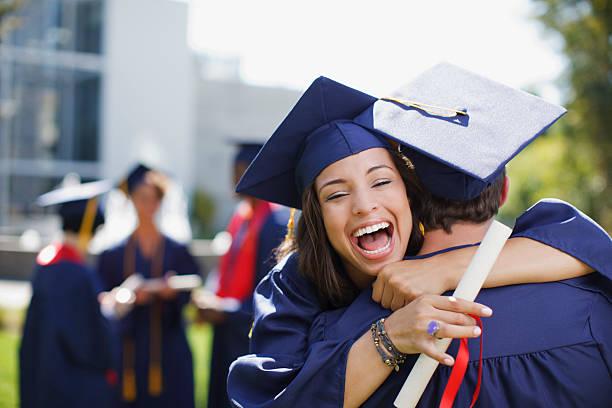 sonriendo egresados, que abrazan al aire libre - graduación fotografías e imágenes de stock