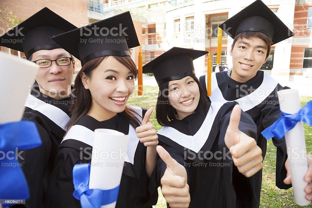 Smiling graduates with diplomas stock photo