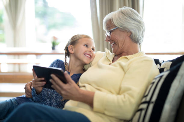 smiling granddaughter and grandmother using digital tablet on sofa - granddaughter and grandmother stock photos and pictures