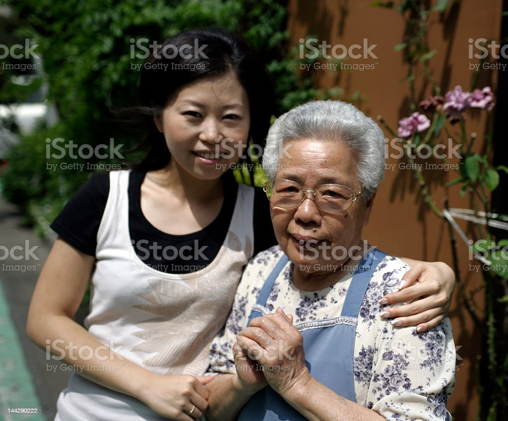 Smiling granddaughter holding grandmother while outdoors royalty-free stock photo