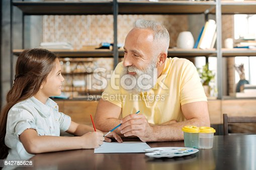 istock Smiling grandfather and granddaughter painting a picture together 842785628