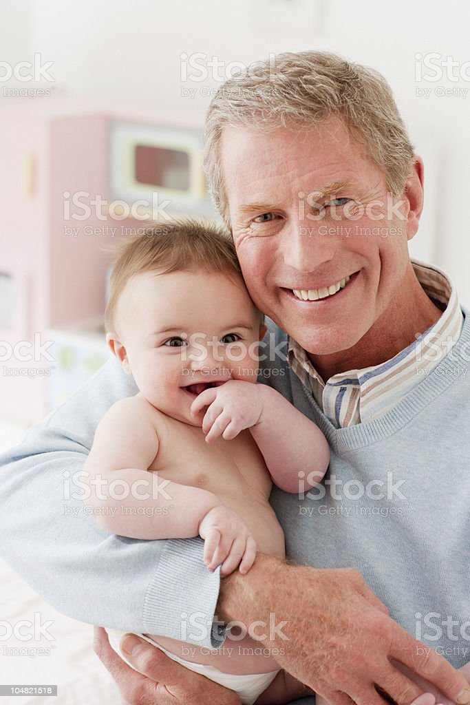 Smiling grandfather holding baby royalty-free stock photo