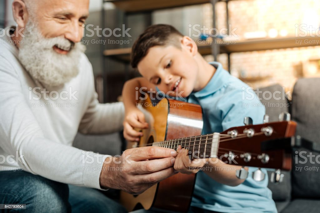 Lächelnden Großvater, Enkel zeigt, wie man Gitarre spielen – Foto