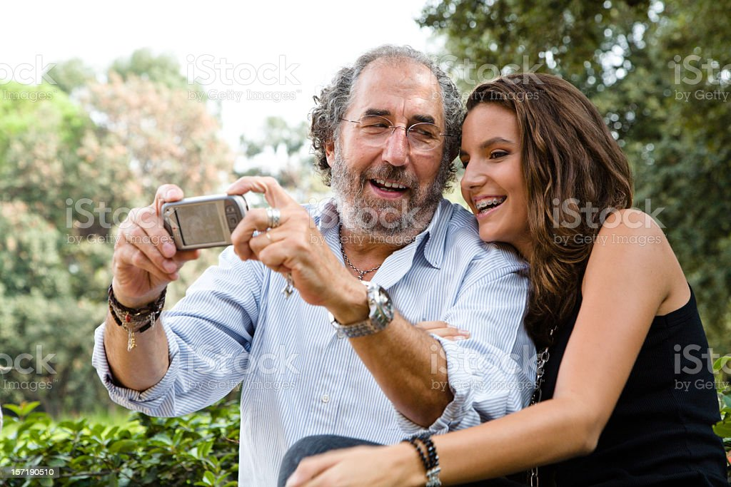 Smiling grandfather with teenager granddaughter taking pictures using cell phone. stock photo