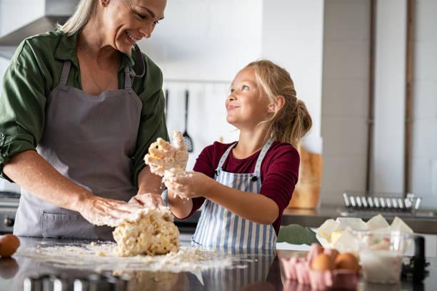 Grand-mère de sourire et enfant heureux pétrissant la pâte - Photo