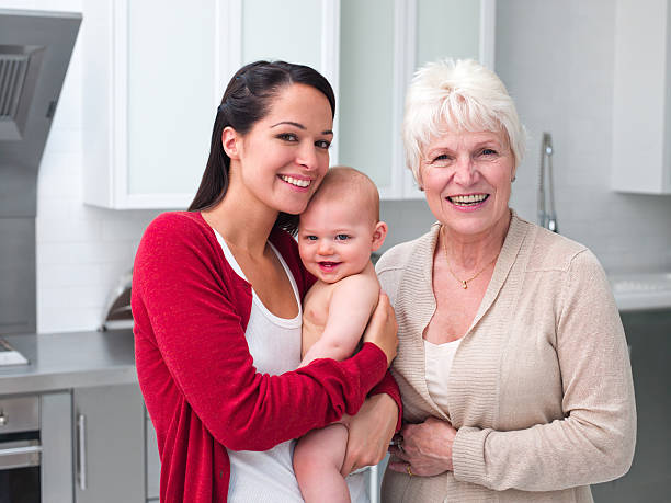 Smiling grandmother and mother holding baby in kitchen stock photo