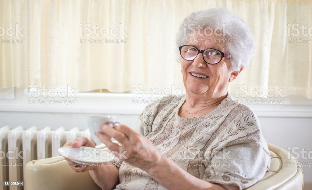 Smiling grandmother drinking coffee at home. stock photo