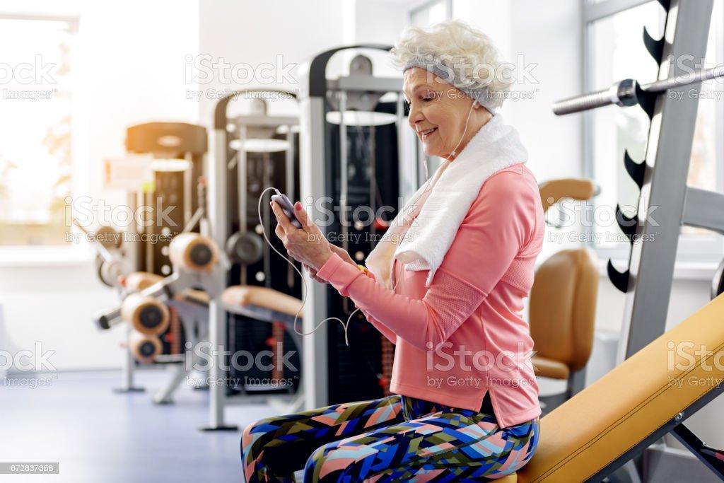 Canción de audición abuela sonriente en gimnasio - foto de stock