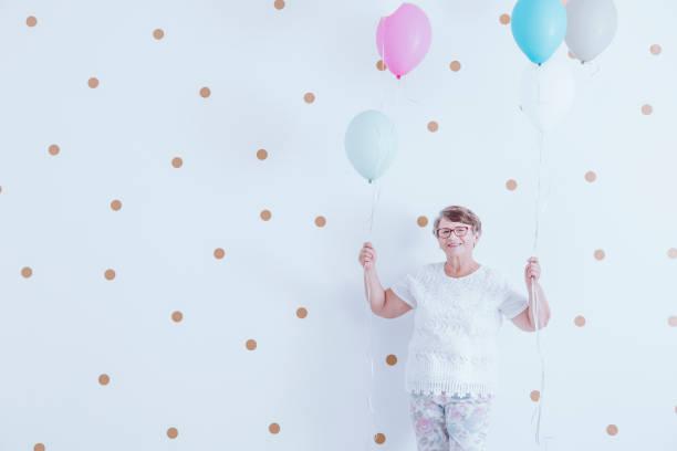 lächelnden großmutter mit bunten luftballons - rentenpunkte stock-fotos und bilder