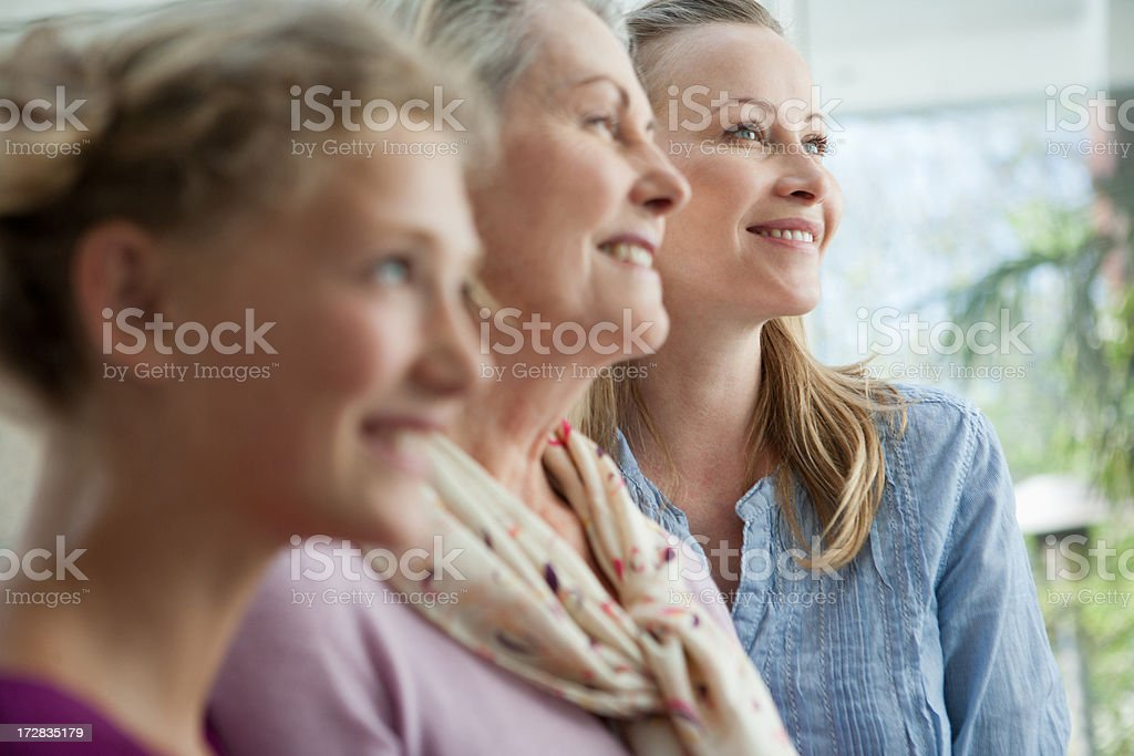 Smiling grandmother, mother and daughter looking up stock photo