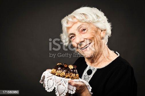 Beautiful senior woman offering a delicious fruitcake