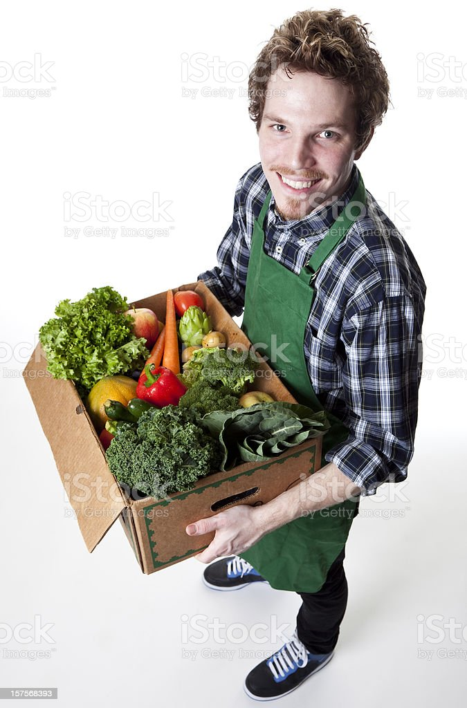 smiling green grocer carrying box of vegetables royalty-free stock photo