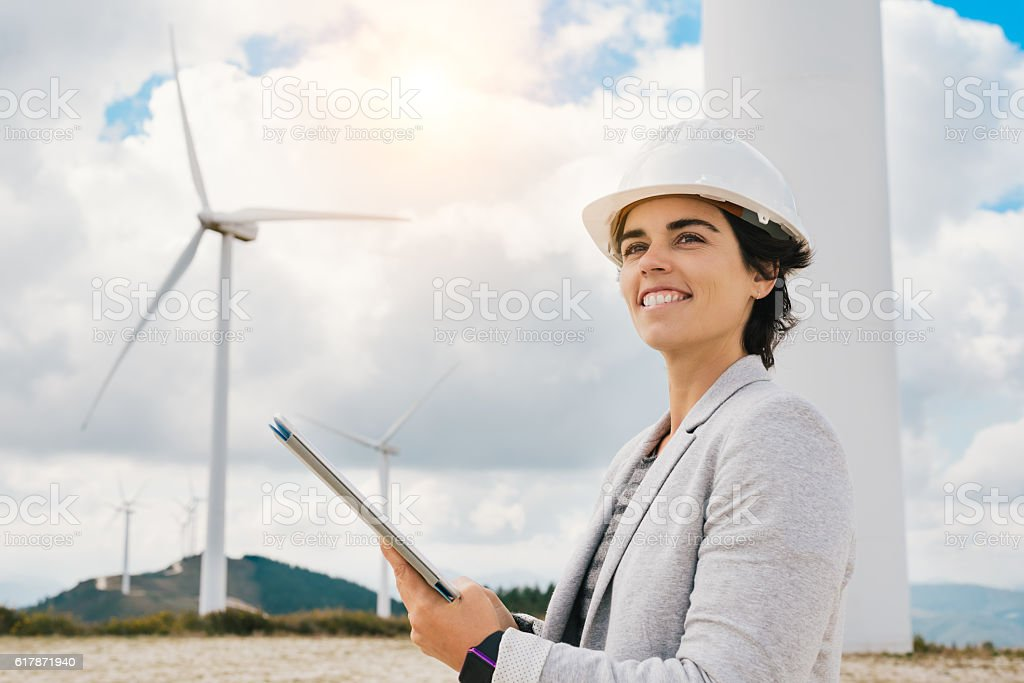 Smiling green indestry engineer woman holding tablet with safety helmet stock photo