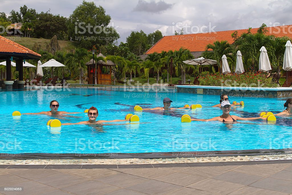 Smiling group doing aqua aerobics in swimming pool with dumbbells stock photo