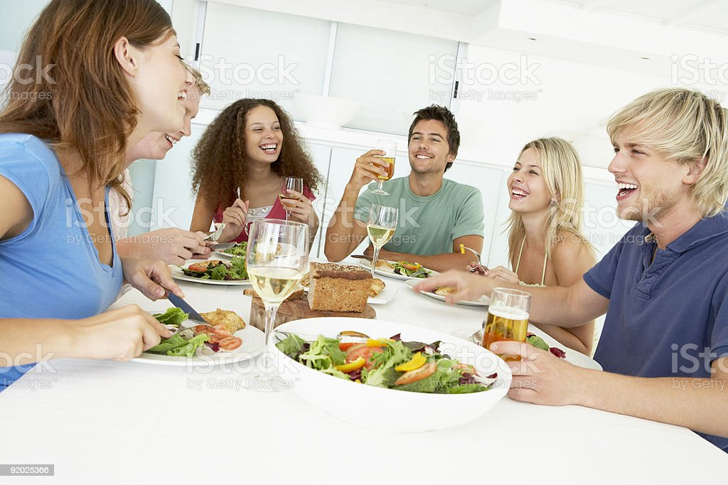 Smiling group eating vegetable lunch and drinking together stock photo