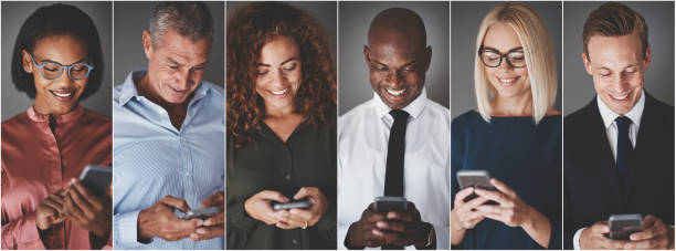 smiling group of diverse businesspeople sending text messages - mandare un sms foto e immagini stock